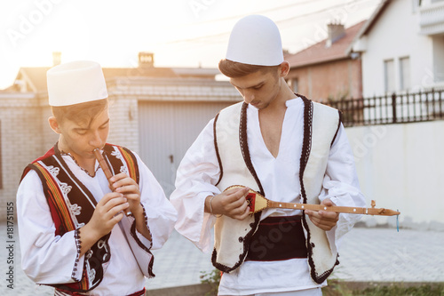 Photo teen boys in traditional albanian costume playing music with flute and string in