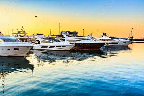 Luxury yachts docked in sea port at sunset. Marine parking of modern motor boats and blue water. Travel and fashionable vacation.