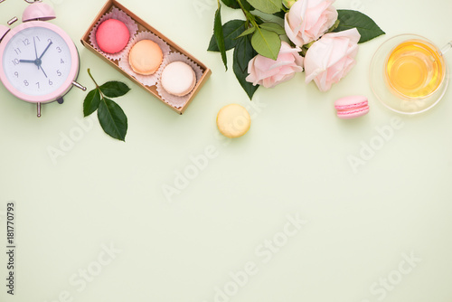 Aluminium Prints Macarons Colorful macaroons and rose flowers with gift box on wooden table. Sweet macarons in gift box. Top view