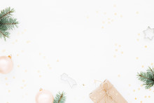 Minimal Styled Christmas Background With Gift Box, Blush Baubles, Fir Branches And Baking Molds On White. Holiday Flat Lay, Top View.