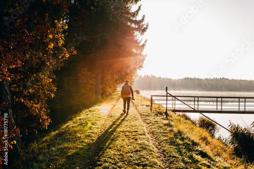 Backpacker in morning light on lakeside