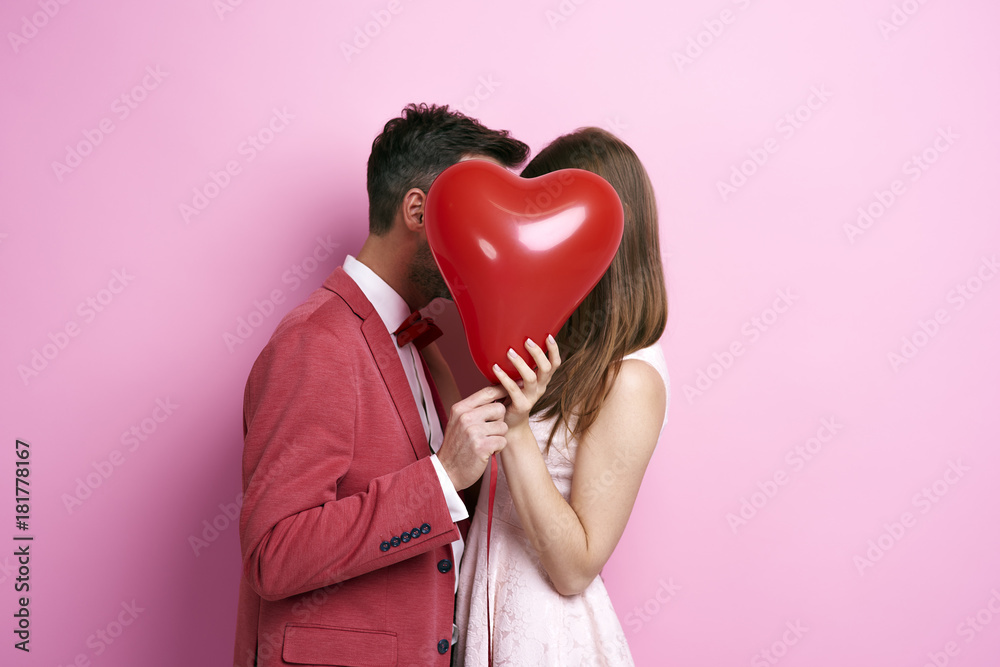 Fotografie, Obraz  Affectionate couple covering face with balloon and kissing