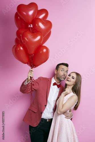 Obraz na plátně  Affectionate couple with heart shape balloons flirting