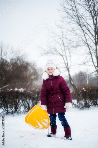 A girl in winter clothes is holding a yellow iceman in her arms Canvas Print
