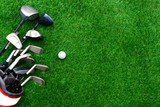 Golf ball and golf club in bag on green grass