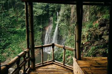 Beautiful waterfall in green forest. View from bamboo wooden house. Nature landscape background