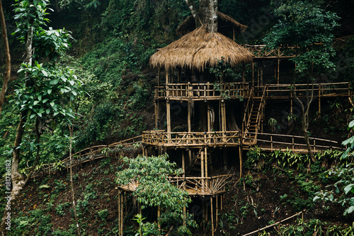 Foto op Plexiglas Bamboe Wooden bamboo hovel house in forest. Film color toned filter