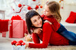 Content woman with little girl having fun while posing among Christmas decor and presents.