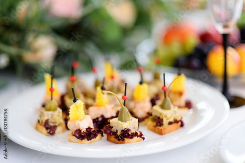 Fototapeta Plates with assorted appetizers on an event party or dinner.