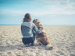 canvas print picture - Young woman sitting on beach with big dog