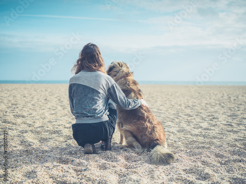 Fototapety, obrazy: Young woman sitting on beach with big dog