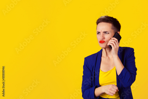 Fotografering  Closeup portrait angry young woman, teenager talking on cell phone, having unpleasant, bad conversation isolated yellow wall background