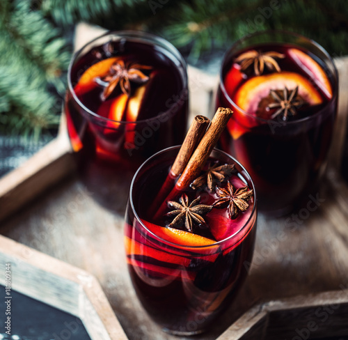 Christmas hot mulled wine in a glass with spices and citrus fruit. Mulled wine with cinnamon, anise and orange.