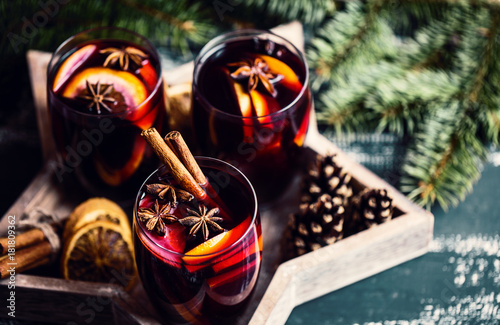 Christmas hot mulled wine in a glass with spices and citrus fruit. Mulled wine with cinnamon, anise and orange. Christmas atmosphere