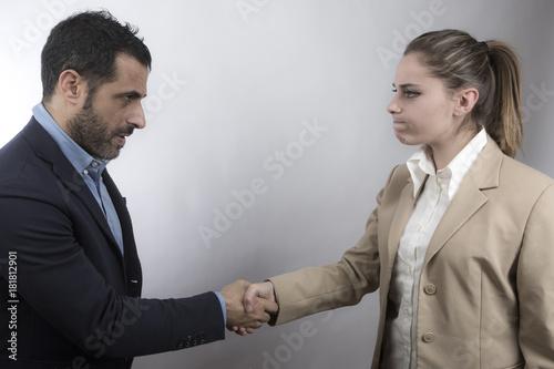 due manager si stringono la mano e guardano in macchina - sfondo bianco
