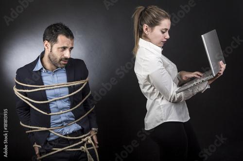 Fototapeta  un uomo triste in giacca è legato mentre la sua compagna controlla il suo comput
