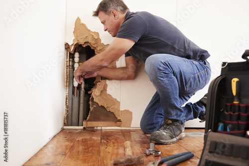 Obraz na plátně  Middle aged man repairing burst water pipe