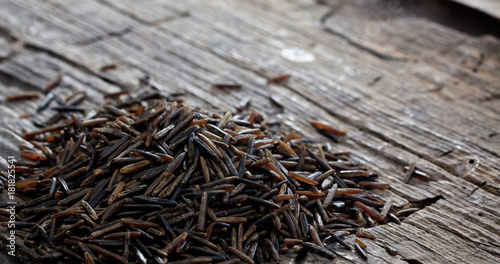 Obraz Heap of raw wild rice on an old wooden table - fototapety do salonu
