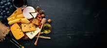 Assortment Of Cheeses, A Bottle Of Wine, Honey, Nuts And Spices, On A Wooden Table. Top View. Free Space For Text.