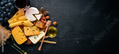 Fototapeta Assortment of cheeses, a bottle of wine, honey, nuts and spices, on a wooden table. Top view. Free space for text. obraz