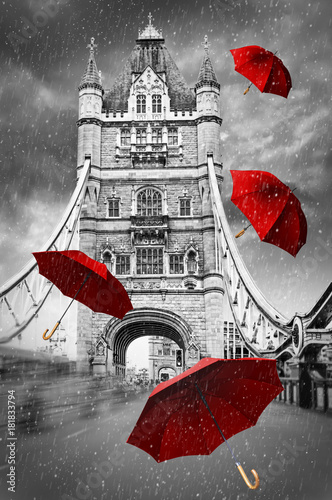 Tower Bridge na Tamizie z latającymi parasolami. Londyn, Anglia. Koncepcja czarno-biała grafika z czerwonym elementem.