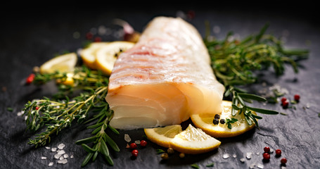 Fototapeta Fresh raw cod fillet with addition of herbs and lemon slices on black stone background