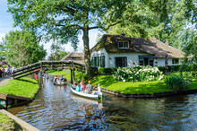 "Giethoorn, Netherlands: View Of Famous Giethoorn Village With Canals And Rustic Thatched Roof Houses.The Beautiful Houses And Gardening City Is Know As ""Venice Of The North"""
