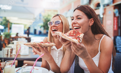 Poster Pizzeria Pizza time. Young girls eating pizza in a cafe. Consumerism, lifestyle
