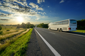 Fototapeta White bus traveling on the asphalt road in a rural landscape at sunset
