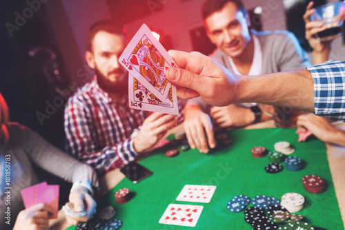 Young people play poker at the table. Wallpaper Mural