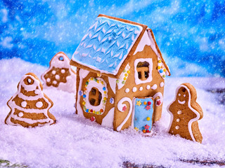 Gingerbread man and Christmas trees cookies in snow about sweet house. Winter background. Xmas decoration food close up