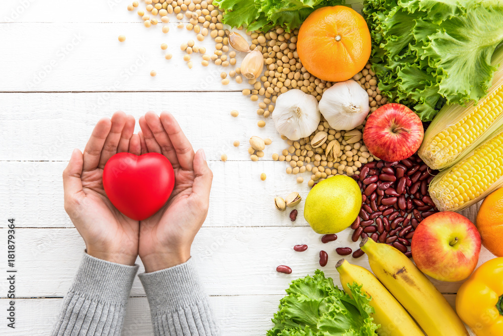 Fototapety, obrazy: Woman hands showing red heart ball with healthy food aside