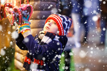 Little Cute Kid Boy Buying Sweets From A Cancy Stand On Christmas Market