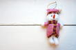 Toy fabric Christmas snowman on wooden background.