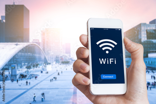 Business person connecting to WiFi hotspot on smartphone screen, city