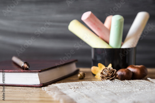 Fotografie, Obraz  Teacher's colorful chalks with school journal and pen on the wooden table at the blackboard in classroom