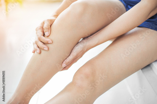 Photo woman suffering from leg pain sit on the floor