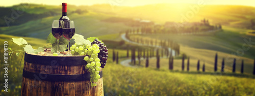 La pose en embrasure Vignoble Red wine bottle and wine glass on wodden barrel. Beautiful Tuscany background