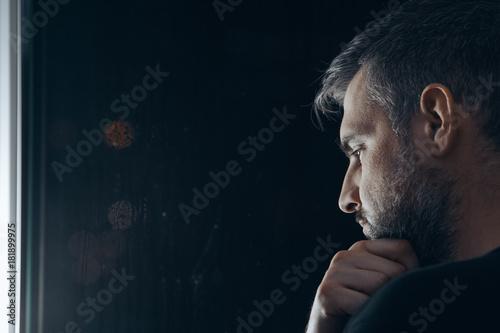Fotografie, Obraz  Man holding chin beside window