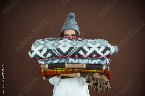 Obraz Woman looking out from pile of blankets - fototapety do salonu