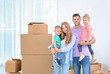 Happy family near moving boxes in their new house