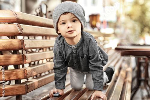 Obraz Adorable little boy on bench in outdoor cafe - fototapety do salonu
