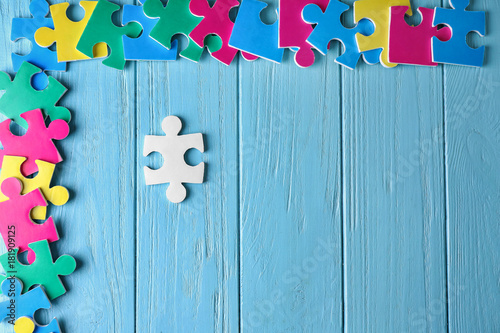 Photo Composition with different puzzles on wooden background