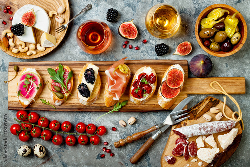 Appetizers table with italian antipasti snacks and wine in glasses. Brushetta or authentic traditional spanish tapas set, cheese variety board over grey concrete background. Top view, flat lay