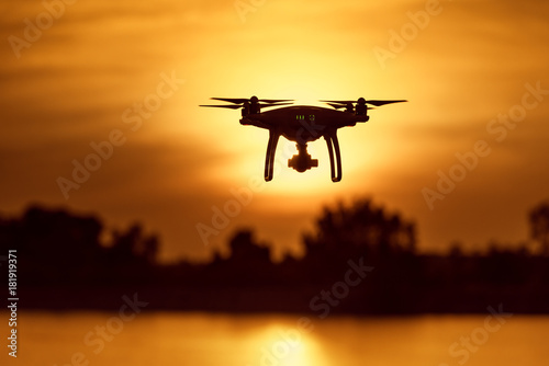 Deurstickers Militair Silhouette of modern RC Drone / Quadcopter with camera flying above the river with tree background at sunset