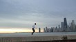 Man starts running from the set position. Man is running on the ebankment. Athlete training outdoors. Downtown with skyscrapers on the background.