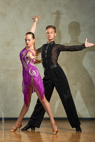 Carta da parati Attractive young couple of children dancing ballroom dance in studio
