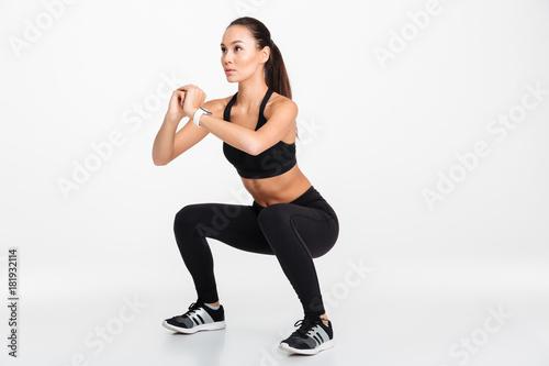 Portrait of a confident asian fitness woman doing squats Canvas Print