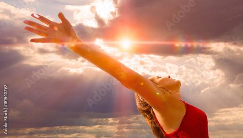 Fotografie, Obraz  Mujer con brazos abbiertos al cielo y puesta de sol