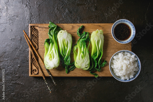 Fototapeta Stir fried bok choy or chinese cabbage with soy sauce and bowl of rice served on decorative wooden cutting board with chopsticks over dark texture background. Top view with space. Asian style dinner obraz